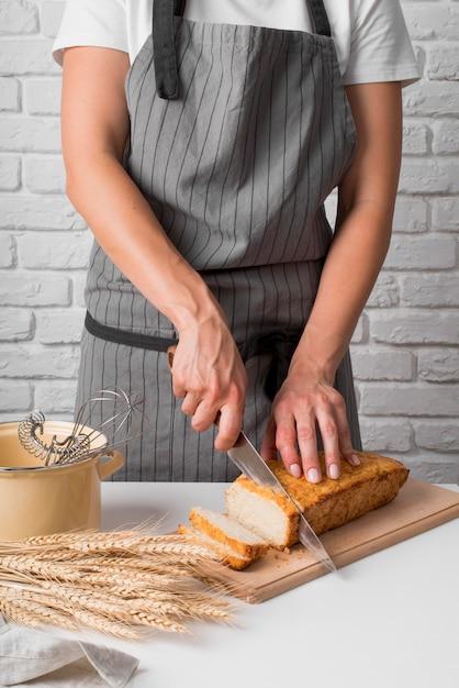 Metà donna del colpo che affetta il pane di banana Foto Gratuite