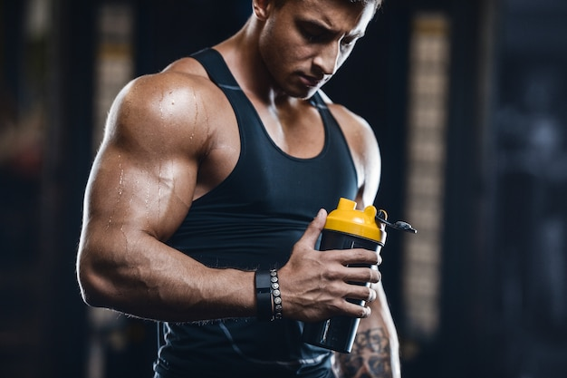 Metta in mostra l'acqua potabile dell'uomo muscolare di forma fisica dopo l'allenamento Foto Premium