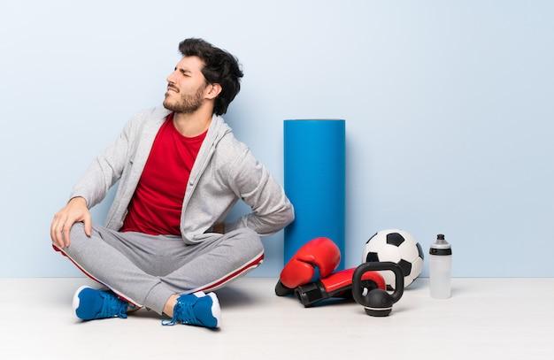 Metta in mostra l'uomo che si siede sul pavimento che soffre di mal di schiena per aver fatto uno sforzo Foto Premium