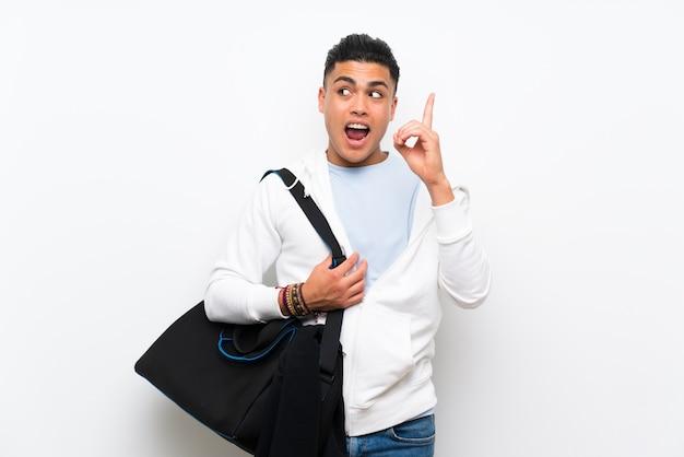 Metta in mostra l'uomo sopra la parete bianca isolata che intende realizzare la soluzione mentre alza un dito su Foto Premium