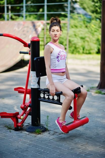 Metta in mostra l'usura della ragazza sulla camicia bianca di american national standard degli shorts che fa gli esercizi sui simulatori all'aperto al parco. Foto Premium