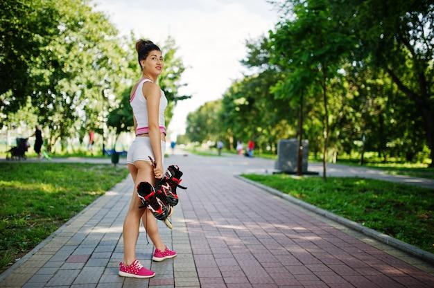 Metta in mostra l'usura della ragazza sulla camicia di american national standard degli shorts con i pattini di rullo al parco. Foto Premium