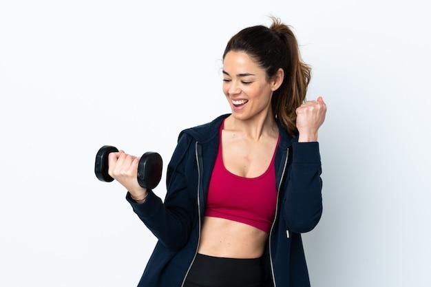 Metta in mostra la donna che fa il sollevamento pesi sopra la parete bianca isolata che celebra una vittoria Foto Premium