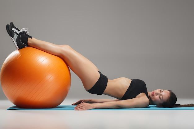 Mette in mostra la donna che fa le esercitazioni su un fitball Foto Gratuite