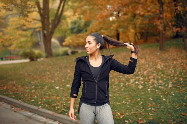 Mette in mostra la ragazza in un addestramento superiore nero in un parco di autunno Foto Gratuite