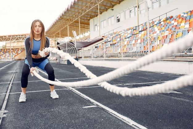 Mette in mostra la ragazza in un addestramento uniforme blu allo stadio con la corda Foto Gratuite