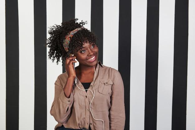 Mettere le cuffie nell'orecchio e stupire la mia musica. la ragazza afroamericana sorrisa sta nello studio con le linee bianche e nere verticali a fondo Foto Gratuite