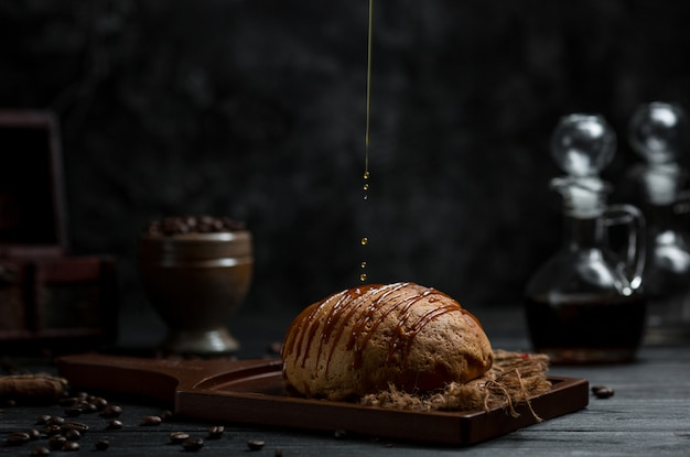 Mettere lo sciroppo di cioccolato in un prodotto da forno dolce Foto Gratuite