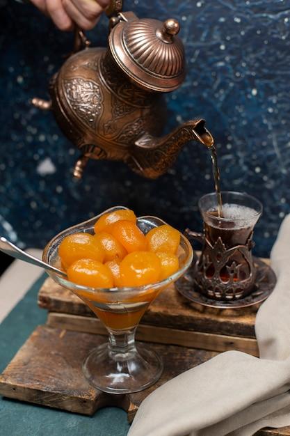 Mettere un bicchiere di tè con confettura di castagne Foto Gratuite