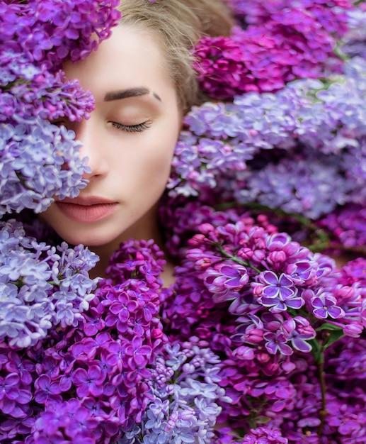 Mezza faccia della giovane ragazza bionda caucasica con gli occhi chiusi, circondata da un sacco di lilla viola e viola, carta da parati, melodia di primavera Foto Gratuite