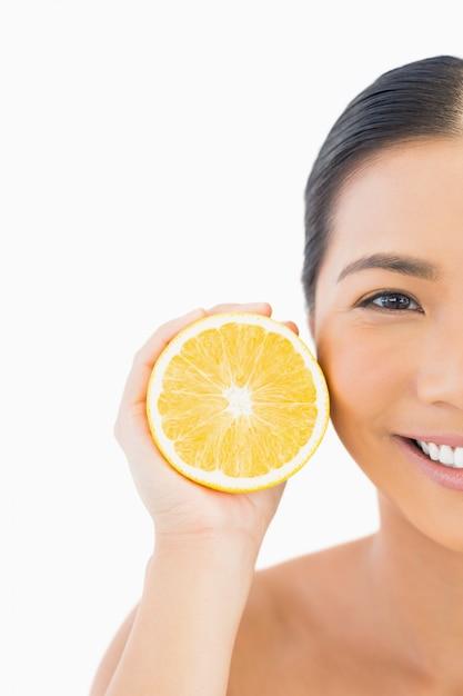 Mezza faccia di sorridente bella donna con orange Foto Premium