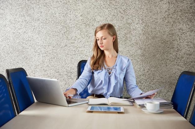 Mezzo busto di donna d'affari seduto alla scrivania, lavorando al computer portatile con documenti Foto Gratuite