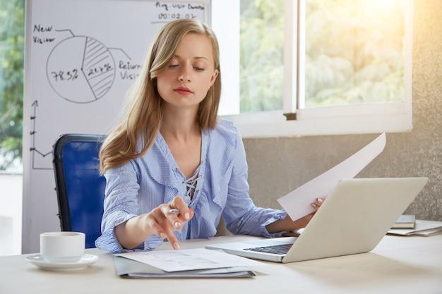 Mezzo busto di giovane businesslady biondo che lavora alla scrivania Foto Gratuite