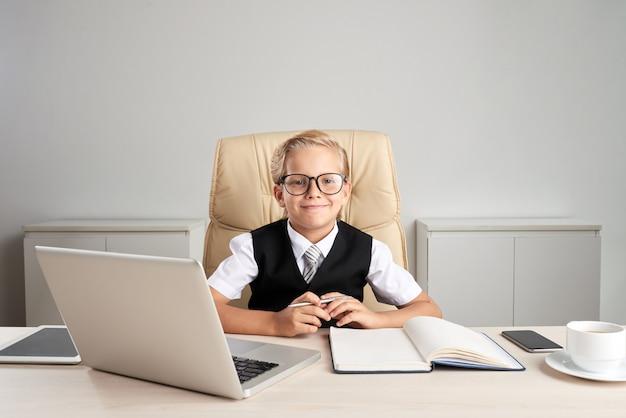 Mezzo busto di piccolo ragazzo biondo caucasico seduto alla scrivania in abiti da cerimonia giocando il grande capo Foto Gratuite