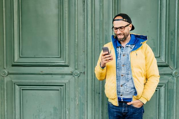 Mezzo busto ritratto di hipster alla moda con la barba vestita in abiti casual tenendo la mano Foto Premium