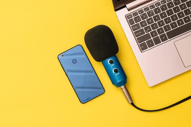 Microfono blu e blu dello smartphone vicino al computer portatile su giallo Foto Premium