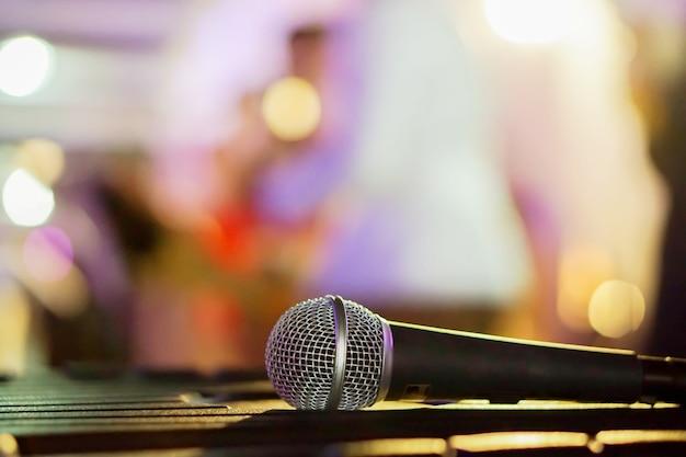 Microfono del primo piano sulla tabella nera in un partito e nella priorità bassa confusa. Foto Premium
