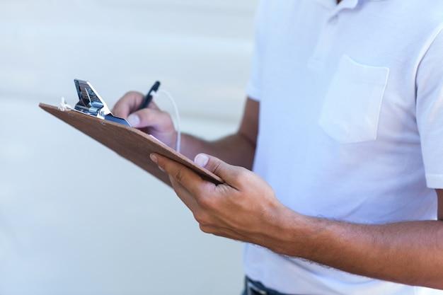 Midsection di consegna uomo scrivere negli appunti Foto Premium