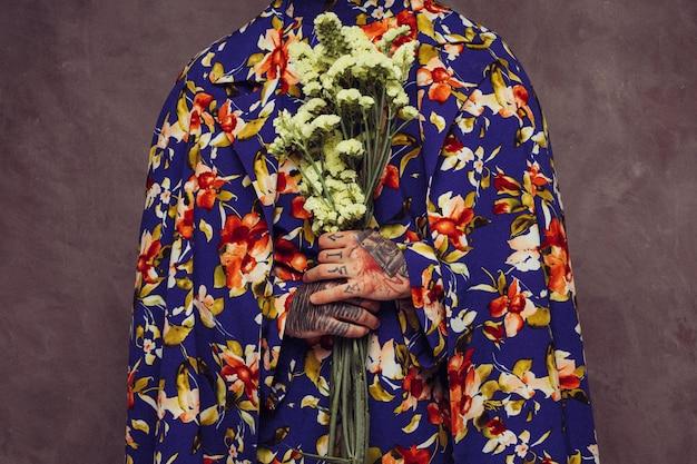 Midsection di un uomo con il tatuaggio nella sua mano che tiene il fiore giallo del limonium Foto Gratuite