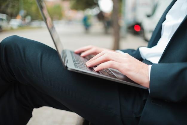 Midsection di un uomo d'affari che scrive sul computer portatile Foto Gratuite