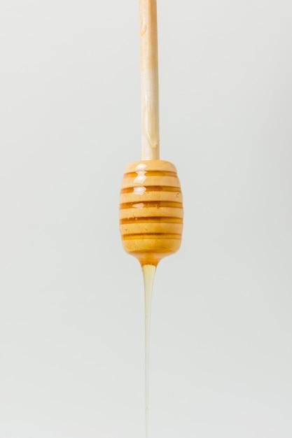 Miele che cade dal cucchiaio Foto Gratuite