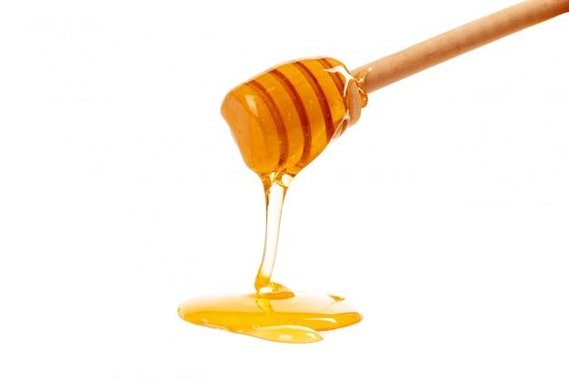 Miele con drizzler in legno isolato su bianco Foto Premium