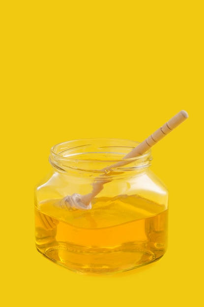 Miele di fiori liquidi in vaso di vetro con cucchiaio di miele in legno. Foto Premium