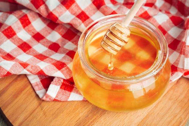 Miele. miele dolce in barattolo di vetro su di legno. Foto Premium