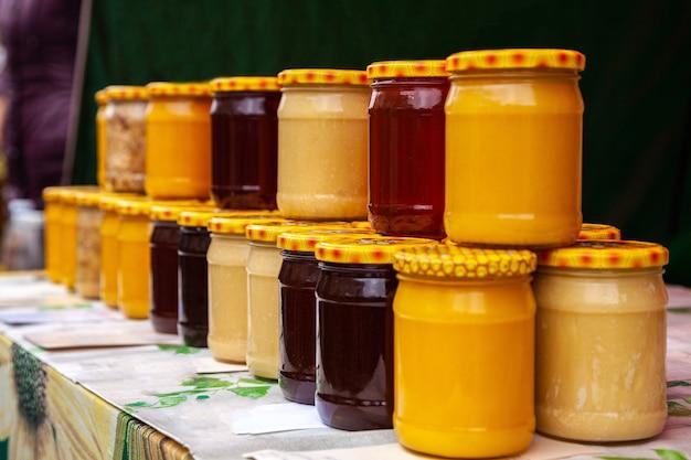 Miele naturale in barattoli di vetro sul mercato. vasetti con vari tipi di miele puro, crudo e fresco. Foto Premium