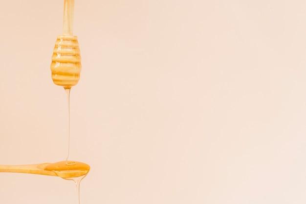 Miele organico del primo piano che versa su un cucchiaio Foto Gratuite