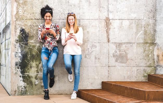 Migliori amici delle ragazze felici divertendosi all'aperto con lo smart phone mobile Foto Premium