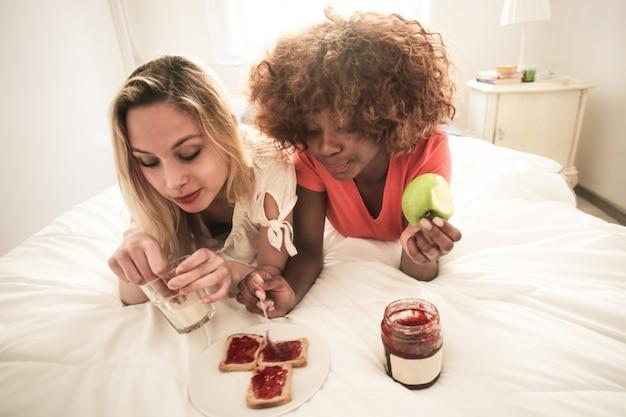 Migliori amici facendo colazione insieme a letto Foto Premium