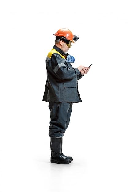 Minatore maschio barbuto senior serio che sta alla macchina fotografica con lo smartphone su un bianco Foto Gratuite