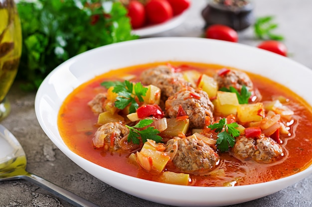 Minestra calda del pomodoro dello stufato con il primo piano delle verdure e delle polpette in una ciotola sulla tavola. zuppa di albondigas, cibo spagnolo e messicano. Foto Premium