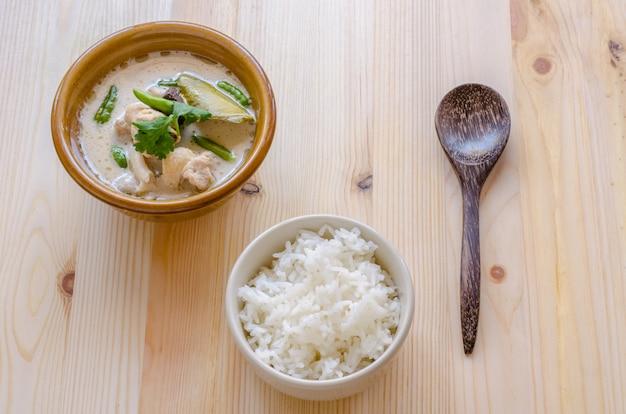 Minestra di pollo tailandese in latte di cocco (tom kha gai) con riso su fondo di legno, alimento tailandese. Foto Premium