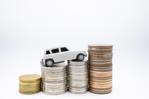 Mini automobile bianca del giocattolo in cima alla pila di monete su bianco. Foto Premium