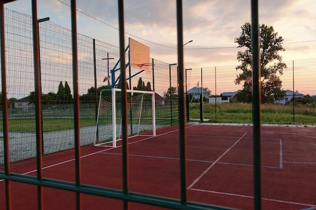 Mini campo da calcio e basket all'aperto con cancello a sfera e cesto circondato da un alto recinto di protezione. Foto Premium