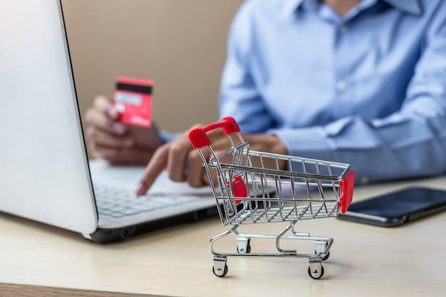 Mini carrello, uomo d'affari asiatico che tiene la carta di credito e usando il portatile Foto Premium