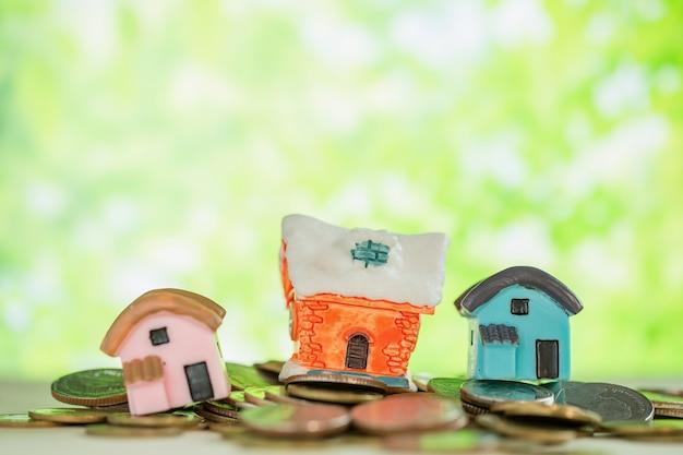 Mini casa sul mucchio delle monete con sfuocatura verde. Foto Gratuite