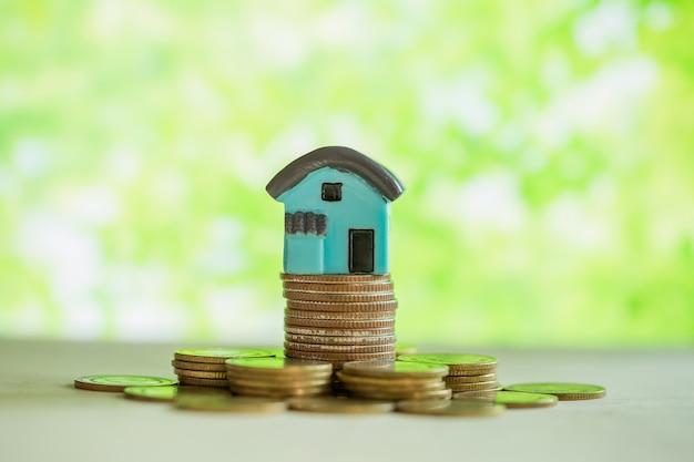 Mini casa sulla pila di monete con sfuocatura verde. Foto Gratuite