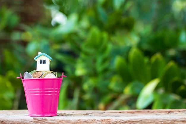 Mini casa sulla pila di monete. concetto di investimento immobiliare. Foto Premium