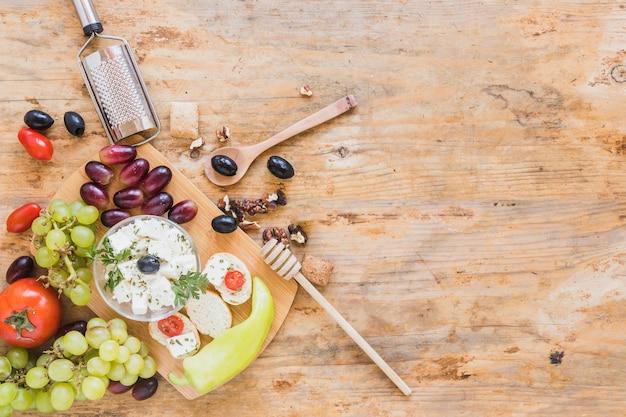 Mini panini con grattugia, cucchiaio e gocciolatore di miele sulla scrivania Foto Gratuite