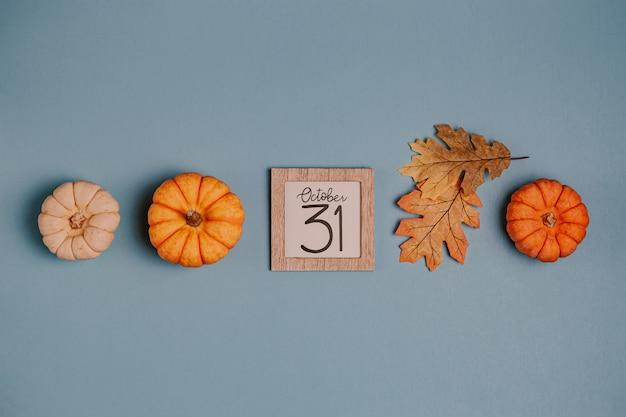 Mini zucche e data di calendario arancio nel telaio di legno Foto Premium