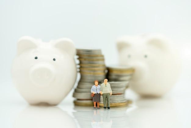 Miniatura degli anziani che stanno con la pila e il porcellino salvadanaio delle monete Foto Premium