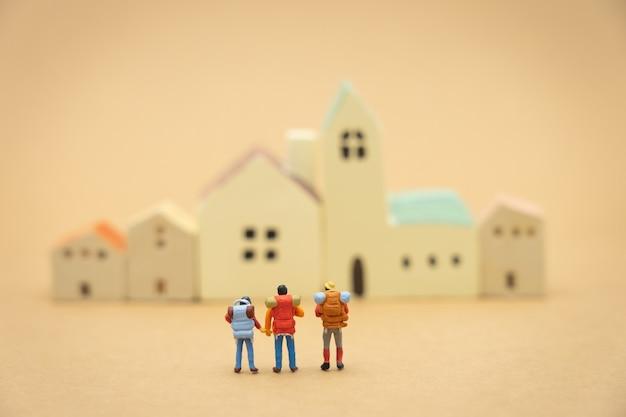 Miniatura di 3 persone sui modelli di casa e hotel per scegliere un posto in cui vivere. Foto Premium