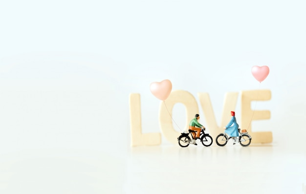 Miniatura di giovani coppie felici in bicicletta con testo