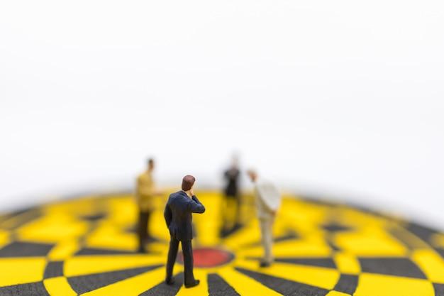 Miniatura di uomo d'affari in piedi e guardando al centro del bersaglio per le freccette giallo e nero Foto Premium