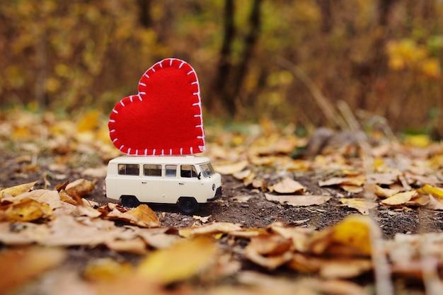 Minivan auto giocattolo fortunato sul tetto di un grande cuore rosso Foto Premium