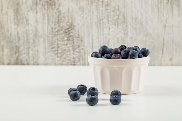 Mirtilli dolci in una vista laterale della ciotola bianca su un lerciume e su un fondo bianco Foto Gratuite
