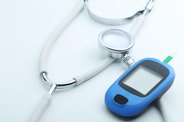 Misuratore di glucosio nel sangue e stetoscopio su sfondo bianco Foto Gratuite